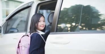 criança entrando em transporte escolar