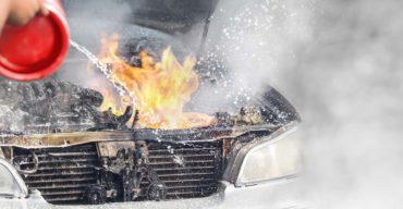 Pessoa tentando apagar fogo após problemas elétricos com carros