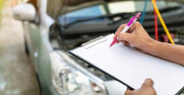 foto de pessoa com prancheta em mãos fazendo anotações em frente a um carro com capô aberto