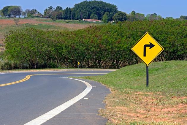 foto de estrada com placa de siga para direita