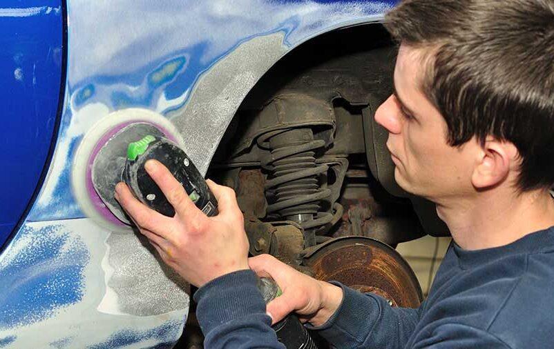 homem realizando serviço de lanternagem no automóvel