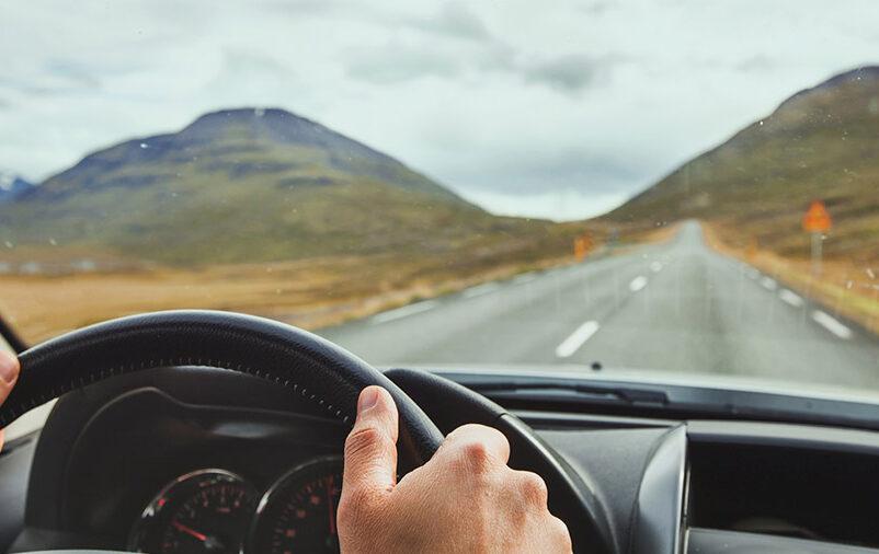 Mãos no volante em uma viagem de carro segura